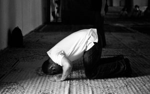 A young man kneeling in prayer at his local mosque